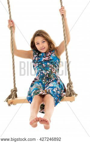 Blonde Girl Swinging On Rope Swing. Full Length Shot Of Pretty Stylish Barefoot Girl Having Fun Agai