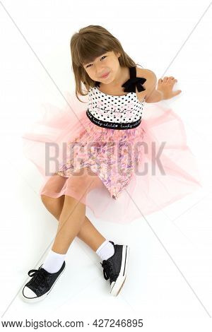 Top View Of Joyful Girl Sitting On Floor. Beautiful Smiling Preteen Girl Sitting With Crossed Legs A