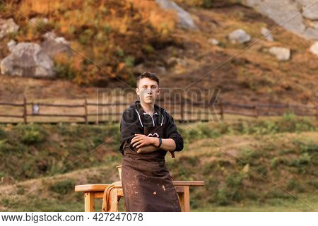 Portrait Of Craftsman In Apron With Crossed Hands Ready To Make Ceramic Pot On Pottery Wheel. Skill