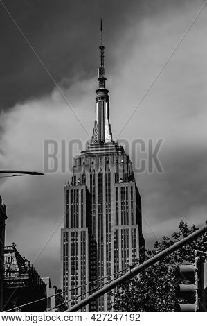 Exterior of the Empire State skyscraper behind buildings, trees and a traffic light under a partly cloudy gray sky in New York City. Grayscale. The focus is on the Empire state building. 7/19/2021