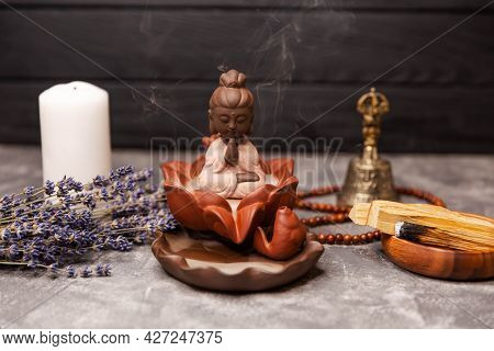 Aromatherapy And Spa. Buddha Figurine With Incense Smoke. Religious Concept. Buddha Statue With Cand