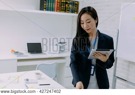 Intent Asian Woman In Jacket Surfing Tablet And Smile While Standing By Desk In Modern Office