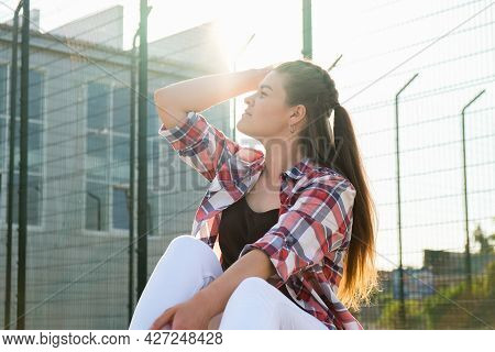 Young Millennial Woman Hippie Sitting On Skateboard. Summer Skate Sessions. Woman Cruising On A Long