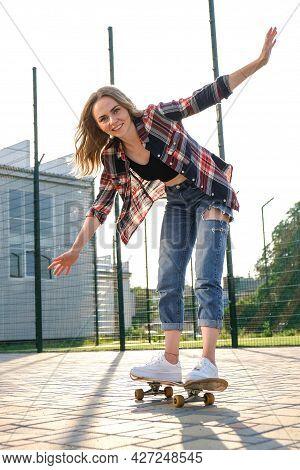 Woman Riding A Skateboard On Street. Skater Girl On A Longboard. Cool Female Skateboarder At Sunset.