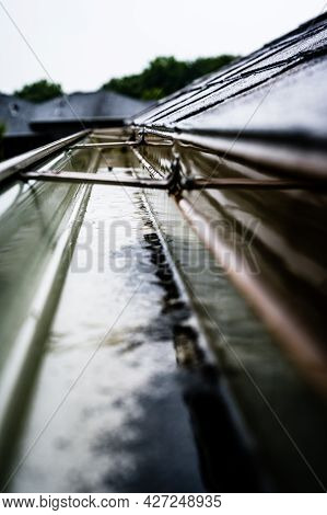Selective Focus On A Section Of Residential Guttering With Hanger Conveying Water During A Storm. Ra