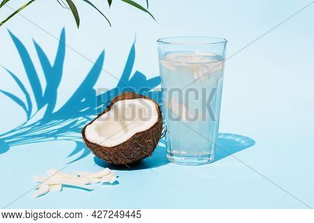 Coconut Water In A Glass With A Cocktail Tube And Half A Fresh Coconut Near On A Blue Background Und