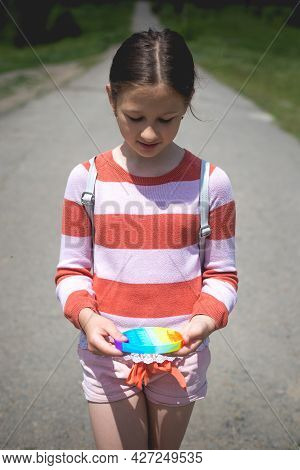 Little Cute Girl Posing In Nature With A Pop-it Antistress Toy In Her Hands.