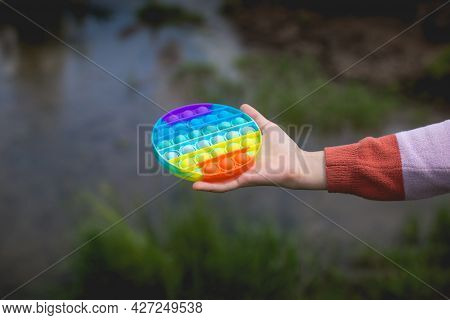 A Little Cute Girl Is Holding A Bright, Colorful Anti-stress Toy Pop It.