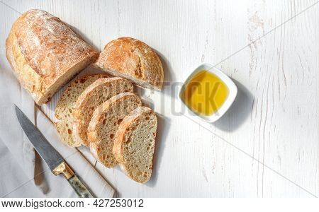 Sliced Organic Bread Ciabatta With Vintage Linen Napkin And Bowl Of Olive Oil On White Wooden Backgr