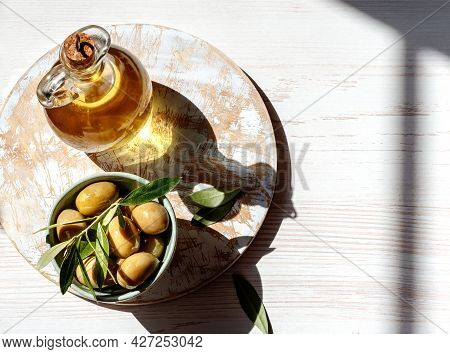 Bottle Of Of Olive Oil With Fresh Olives And Olive Branch On White Wooden Board. Top View Of Olive O