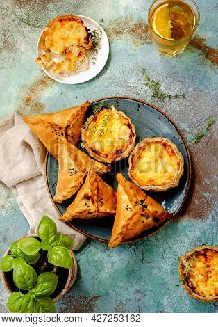 Mini Quiches On A Blue Plate With Glass Of Cold Tea. Flaky Dough Pies. Samosa, Samsa Meat Stuffed Pi