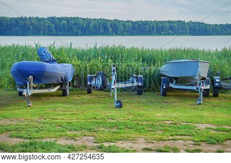 An Inflatable Boat With A Motor In A Cover And A Plastic Boat On Carts On The Lake Coast. Boat Stora