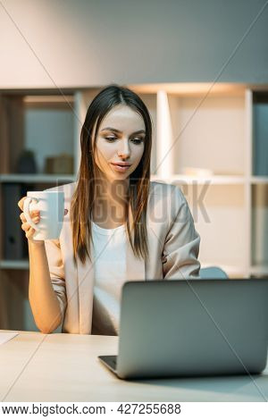 Relaxed Routine Office Work. White Collar Lifestyle. Woman Sitting At Desk Drinking Tea Or Coffee Pr