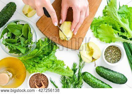 Woman Cooking Salad Of Fresh Green Vegetables And Herbs. Raw Food Concept. Vegan Menu. Cooking Healt