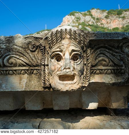 Theatrical mask stone carving of ancient town of Myra in Lycia region, Ruins of ancient city of Myra in Demre, Turkey