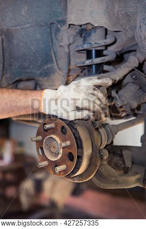 A Mans Gloved Hand Holds A Rusty Car Wheel Hub. In The Garage, A Man Changes Parts On A Vehicle. Sma