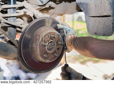 The Hands Of A Gloved Man With A Screwdriver Remove The Caliper On The Hub. In The Garage, A Man Cha