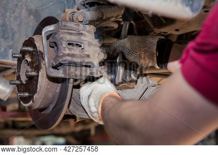 Close-up Male Hands Install Or Remove The Caliper On The Wheel Of An Old Car. In The Garage, A Man C