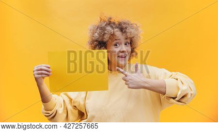 Girl Holding A Yellow Sheet Of Paper Pointing At The Paper. Isolated Girl Over A Bright Yellow Backg