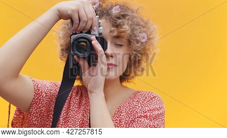 Attractive Girl Holding A Vintage Camera Taking A Picture. Girl In A Joyful Mood Over Bright Yellow