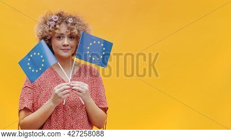 Girl Holding Two Small European Union Flags In Her Hand. Girl Isolated Over A Bright Yellow Backgrou