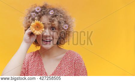 Young Attractive Girl Posing With Orange Gerbera Daisy Flower. Covering Her Eye With Daisy. Isolated