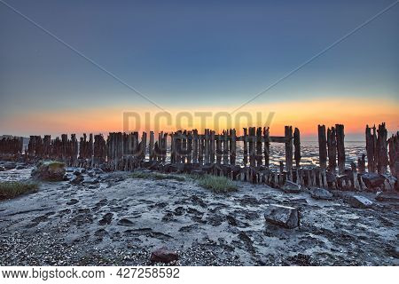 View Of The Wadden Sea During Sunset, At Low Tide. Wooden Posts As A Silhouette In The Mud. Unesco.