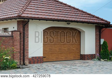 Brown Vertical Blinds Entrance To The Garage. Closed Roller Shutter Door. White Building Under A Bro