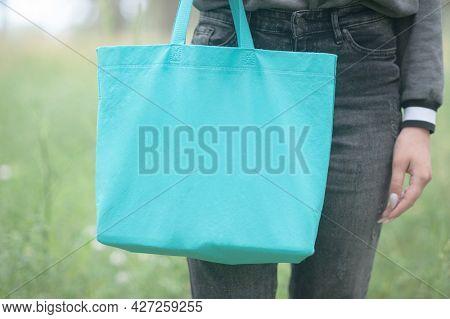 Young woman holding emerald green shopper bag, no face, eco lifestyle concept