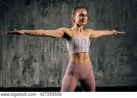 Middle Shot Portrait Of Smiling Muscular Young Athletic Woman With Perfect Body In Sportswear Doing