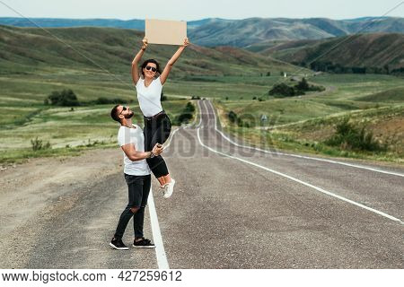 A Young Couple Is Voting On The Road. A Happy Couple Hitchhiking And Voting With A Sign On The Road.