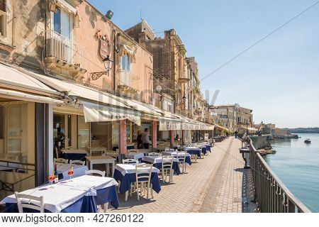 Siracusa, Italy - March 11, 2020: Cozy waterfront cafes and restaurants in Siracusa old town Ortygia, Sicily, Italy