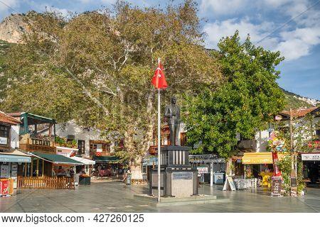 Kas, Turkey - December 2, 2020: Main square of the mediterranean town Kas in Turkey. Cozy outdoor cafes and restaurants at evening in Kas, Turkey. Statue of Mustafa Kemal Ataturk