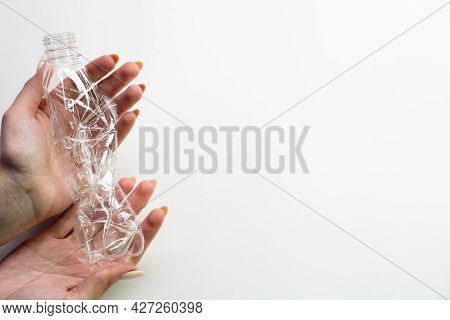 Plastic Trash. World Pollution. Respecting Environment. Woman Hands Holding Used Crushed Bottle Isol