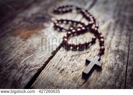 Rosary beads and religious crucifix cross with copy space background