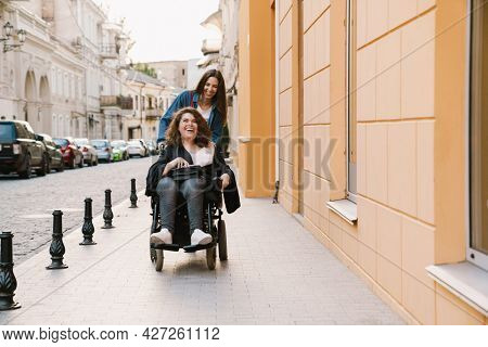 Young woman pushing wheelchair with girl while walking at city street