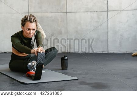 Young sportswoman with prosthesis doing exercise while working out indoors