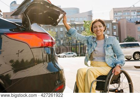 Smiling mid aged woman in wheelchair opening back door of her car outdoors
