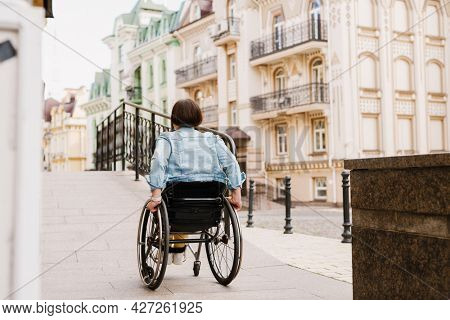 Mid aged brunette disabled woman sitting in a wheelchair standing near accessible entrance to the building back view