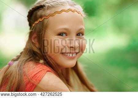 Happy child. Close-up portrait of a laughing happy girl child on a blurred summer background.