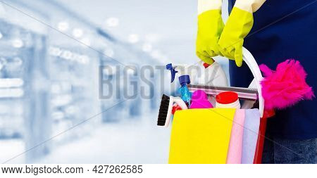 Cleaner With Cleaning Products In Shopping Centre. A Cleaning Lady Stands On A Blurry Background Wit