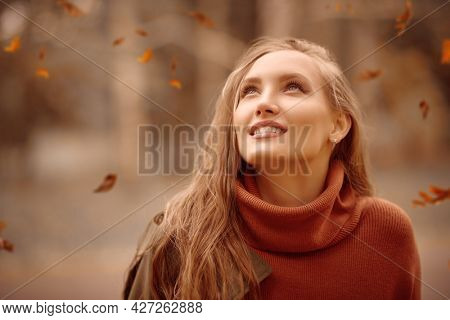 Autumn beauty woman. Portrait of a happy beautiful young woman looking up the leaves flying from above. Autumn colors. Makeup and cosmetics.