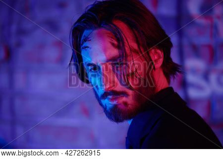 Close-up portrait of a wounded action hero man on his face with bloody scars in multicolour light of the night city.