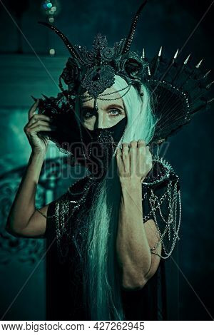 A portrait of fabulous old woman with long gray hair, in a rich headdress and a rich black dress on vintage background. Black Queen, Witch. Halloween.