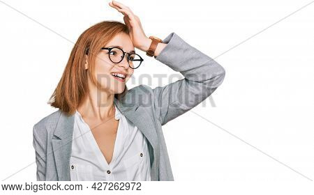 Young caucasian woman wearing business style and glasses smiling confident touching hair with hand up gesture, posing attractive and fashionable