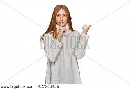 Young irish woman wearing casual winter sweater asking to be quiet with finger on lips pointing with hand to the side. silence and secret concept.