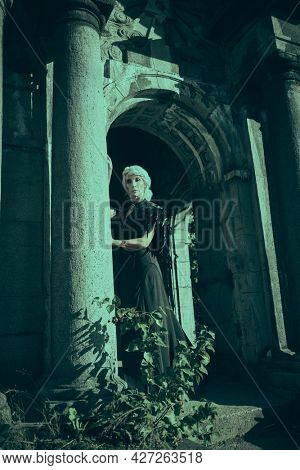 An aristocratic old widow woman with beautiful gray hair and a rich black dress poses sad in a crypt in a cemetery. Black Widow. Atmosphere of mysticism. Halloween.