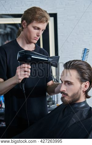 Male beauty. Master barber does the hairstyle and styling with dryer, dries hair to a handsome male client. Barbershop.