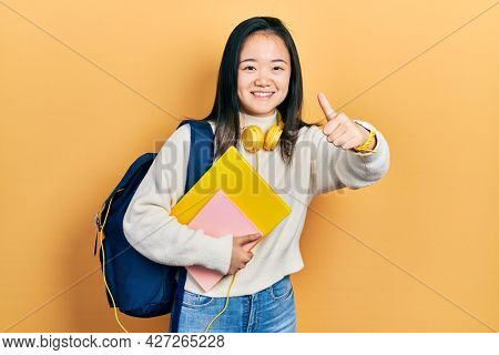 Young chinese girl holding student backpack and books approving doing positive gesture with hand, thumbs up smiling and happy for success. winner gesture.