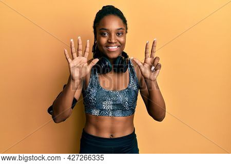 African american woman with braided hair wearing sportswear and arm band showing and pointing up with fingers number eight while smiling confident and happy.